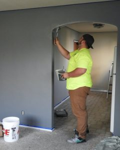 Man in yellow shirt painting interior home wall.