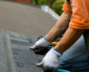Answering the question of what tpe of roof shingles is the best about asphalt showing roofer working with asphalt shingles.