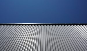 Example of what type of roof shingles is best showing a metal roof with a dark blue sky.
