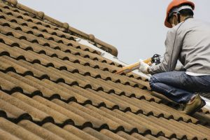 Example of what type of roof shingles is the best showing roofer working with tile on rooftop.